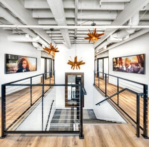 staircase view of Bountiful studio salon suites with ceiling features and portraits on walls